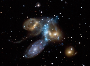 This composite image of X-rays from Chandra (colored light blue) and optical data from the Canada-France-Hawaii Telescope (yellow, red, white, and blue) shows a beautiful new look at the compact group of galaxies known as Stephan's Quintet. One galaxy is thought to be passing through the others at almost two million miles per hour. This generates a shock wave that heats the gas and creates the ridge of X-ray emission detected by Chandra.